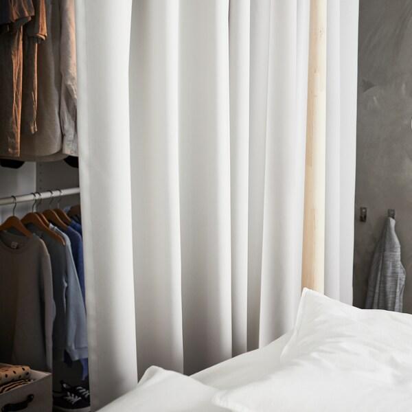 Svetlosivé zatemňovacie závesy MAJGULL, ktoré sa používajú ako predel medzi šatníkom so šatami zavesenými na koľajniciach a posteľou.