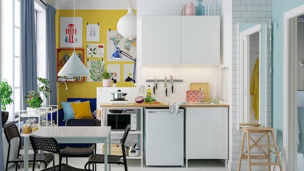 Světlý malý kuchyňský kout s bílou kombinací kuchyně ENHET, bílým jídelním stolem a čtyřmi černými židlemi.