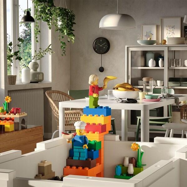 Světlý obývací pokok s bílým stolem, bílými vitrínami a dětskou stavebnicí