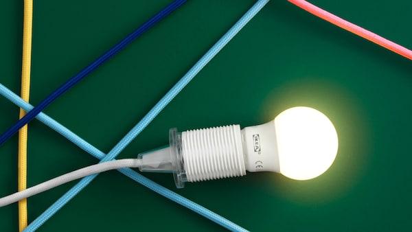 Svietiaca žiarovka LED na zelenom pozadí.