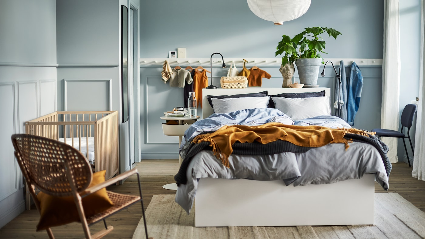 Svijetloplava spavaća soba s bijelim krevetom, bijelom lampom, bijelom pločom s kukama, stolicom za ljuljanje od ratana i SNIGLAR krevetićem.