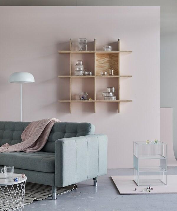 صوفا LANDSKRONA ورفوف حائط مملوءة قليلاً في غرفة جلوس ذات ألوان شاحبة.