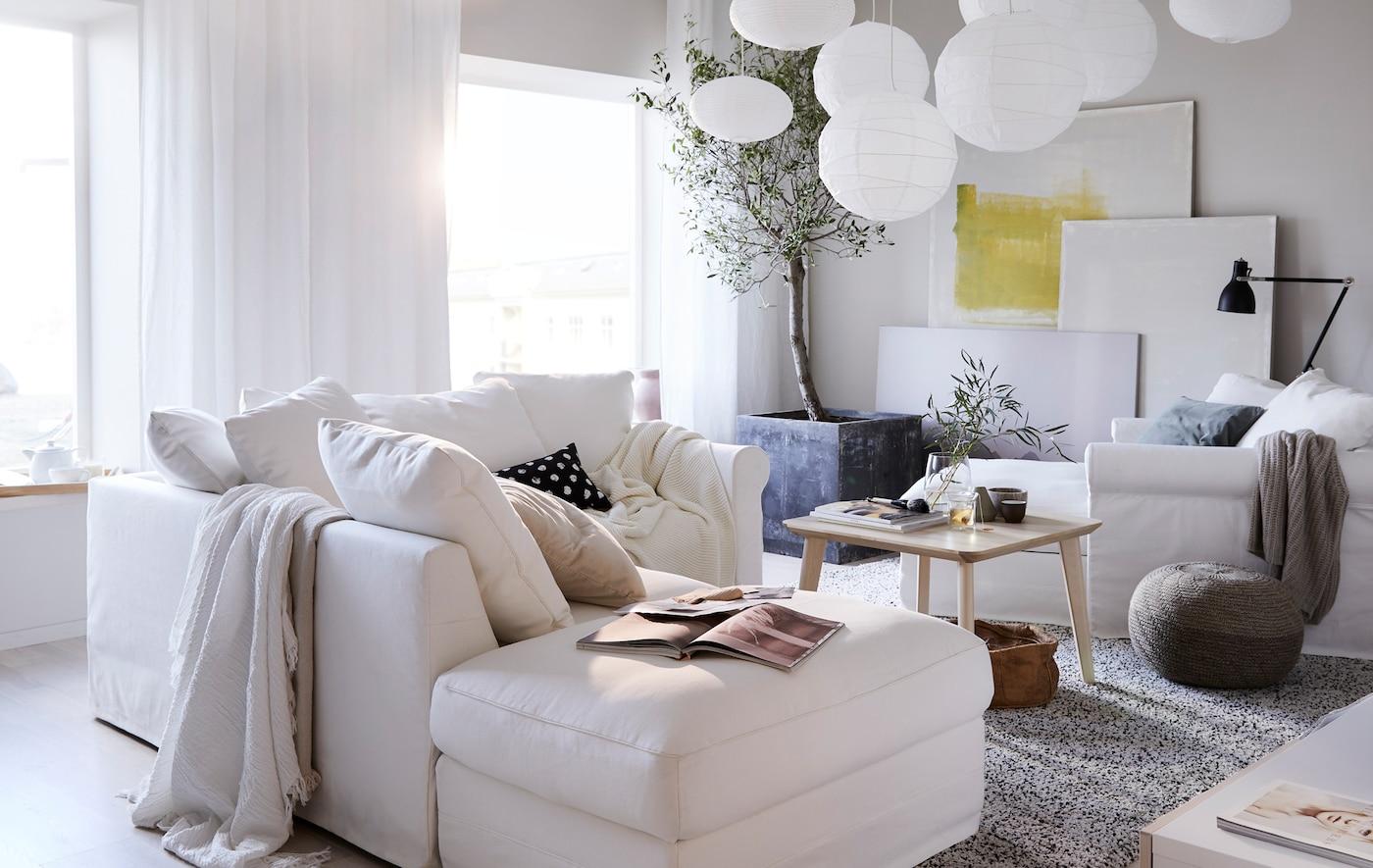 صوفا زاوية GRÖNLID 3 مقاعد من ايكيا في غرفة جلوس بها الكثير من أغطية المصابيح البيضاء المعلّقة وأعمال فنية أمام الحائط.