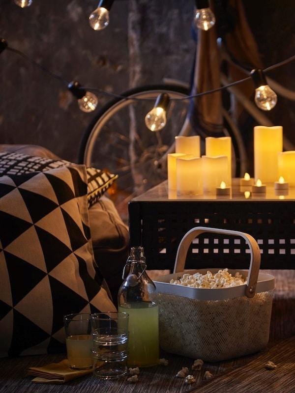 Świece bryłowe LED na stoliku ogrodowym KUNGSHOLMEN, koszyk popcornu i butelka.