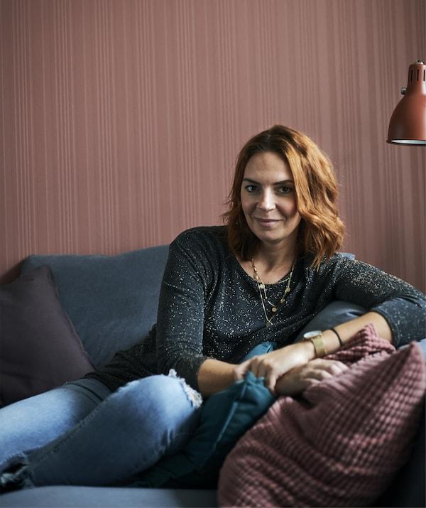 صورة Amélie وهي تجلس على كنبة رمادية اللون أمام جدار أحمر.