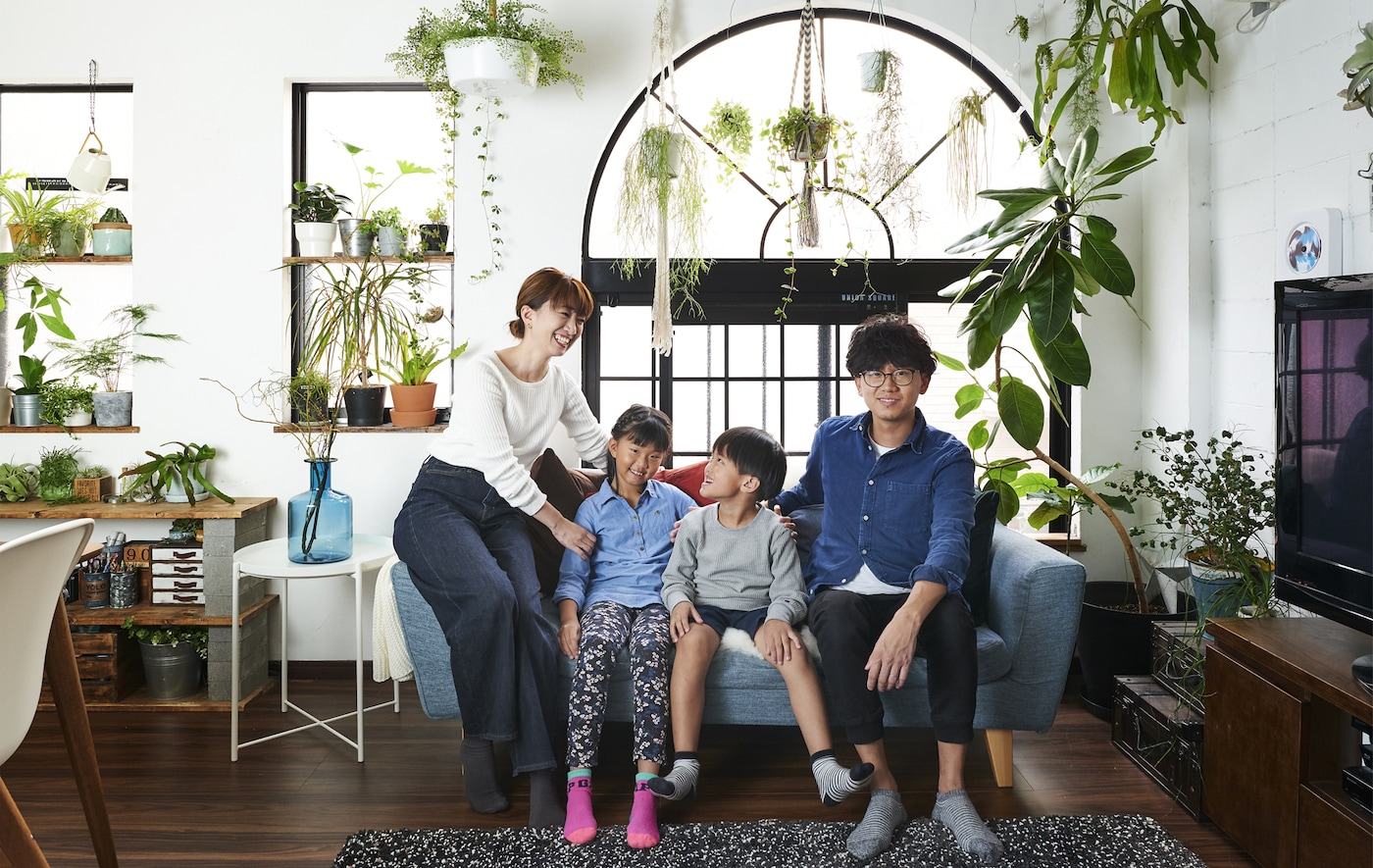 صورة هيرومي وشونسوكي وأطفالهما جالسين على كنبة والنباتات معروضة في النوافذ الخلفية.