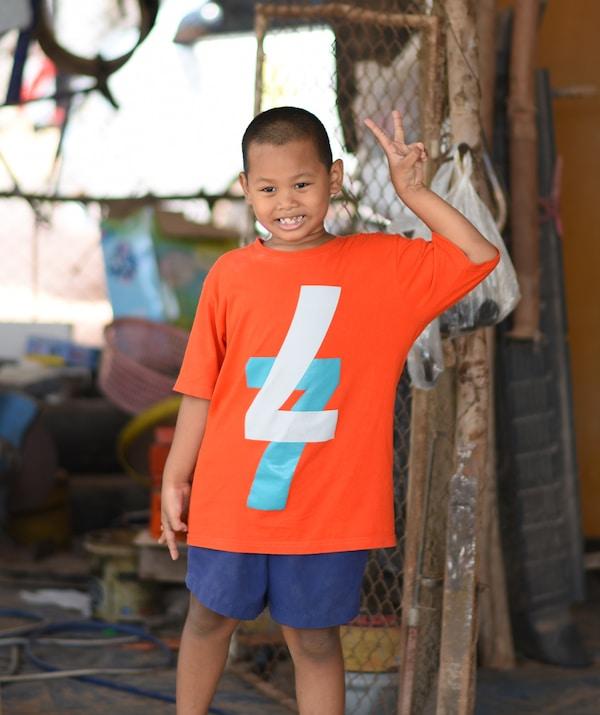 صورة لصبي يصنع علامة السلام بأصابعه.