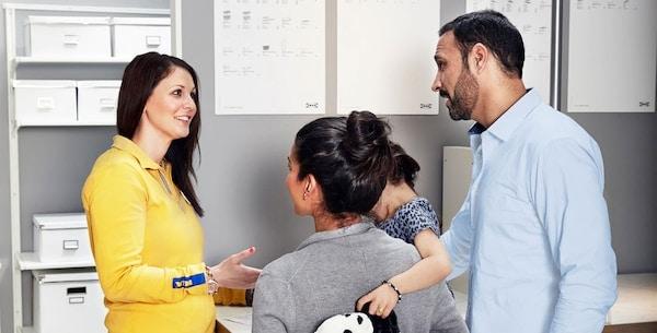 صورة لزميل في العمل يساعد اثنين من العملاء وطفل صغير.