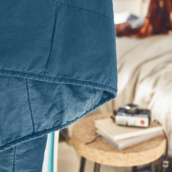 صورة مقربة لغطاء سرير مع ديكور داخلي بلون محايد في الخلفية.