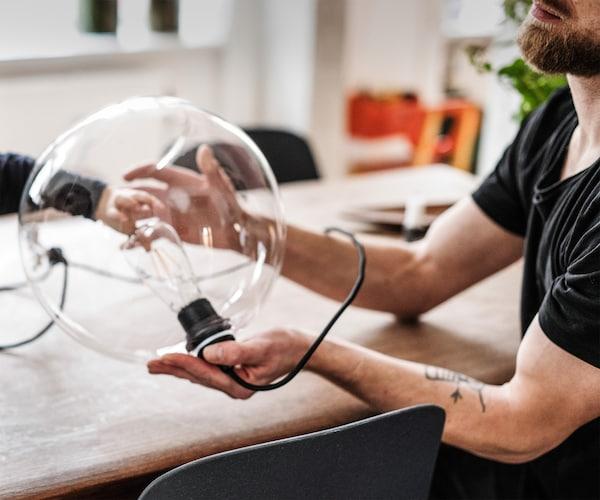 صورة مقربة لرجل يجلس على طاولة ويحمل مصباح طاولة زجاجي كبير.