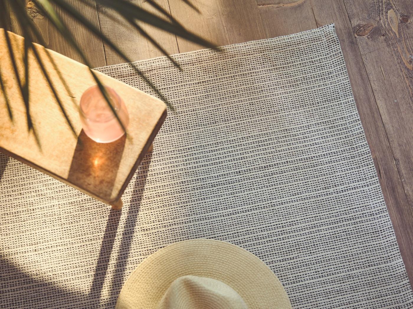 صورة مقربة لسجادة TIPHEDE حياكة مسطحة مع طاولة جانبية عليها قبعة كبيرة، بينما ينساب ضوء الشمس على أحد الجانبين.