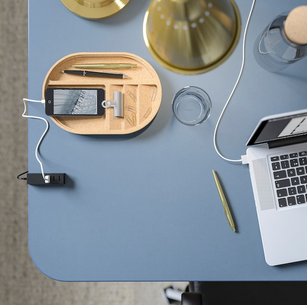 صورة مقربة لسطح طاولة BEKANT مشمع من ايكيا باللون الأزرق مع تابليت وهاتف وبعض اللوازم المكتبية.