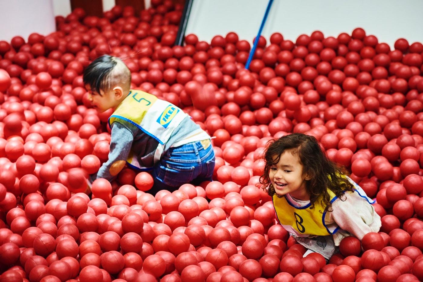 صورة تظهر طفلين يلعبان بسمك على حفرة الكرة.