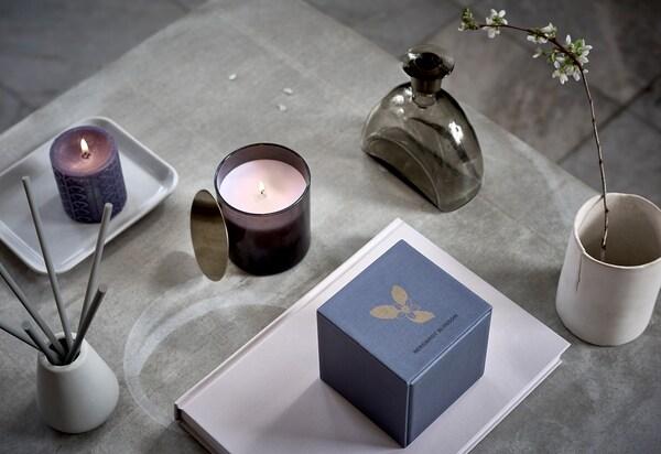 Symetricky rozmístěné voňavé svíčky, dva hrnečky s větvičkami a další dekorace typické pro lázně