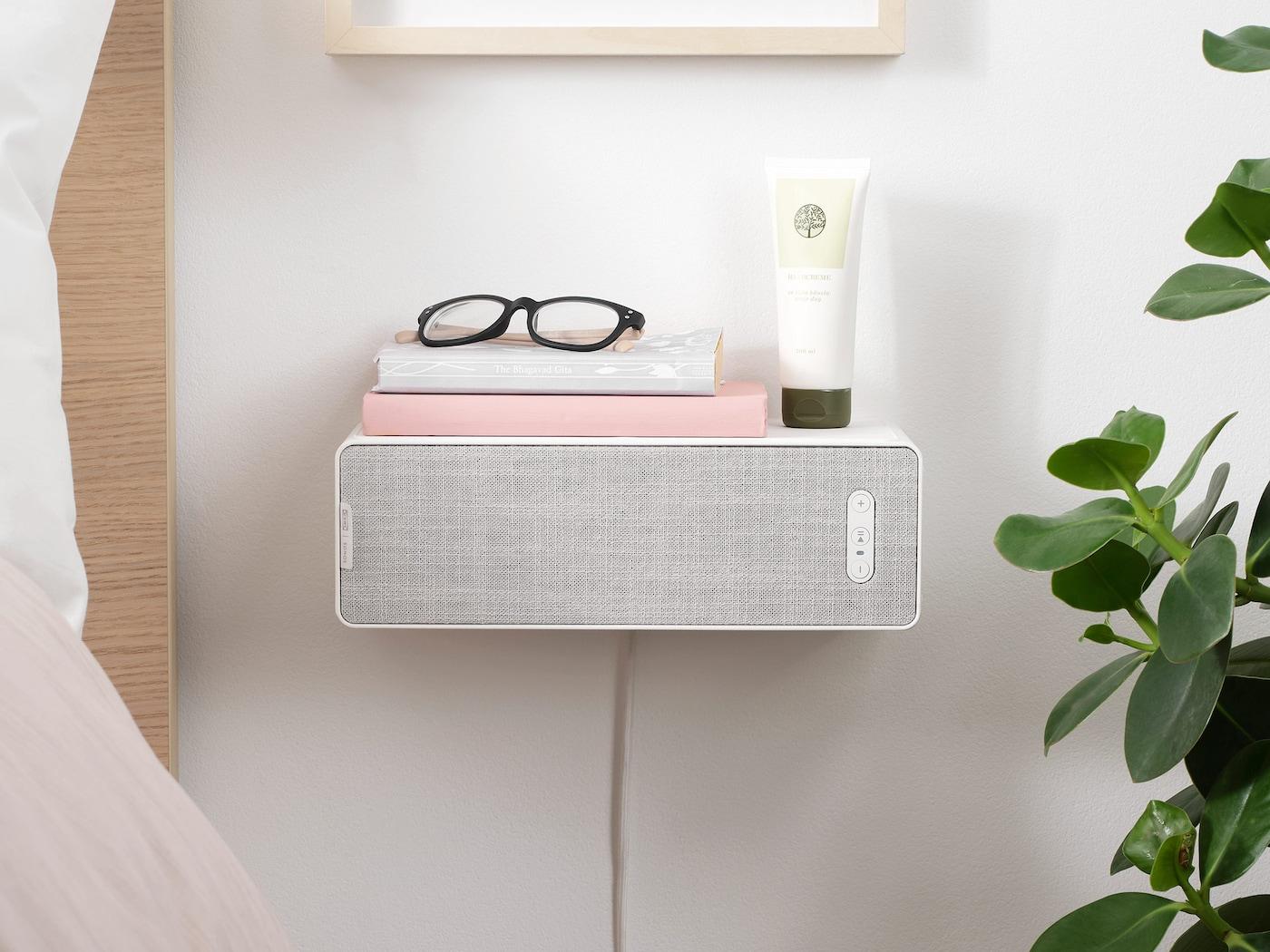 SYMFONISK bokhyllehøyttaler montert på en vegg og brukt som nattbord ved siden av ei seng.