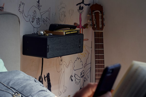 SYMFONISK bookshelf speaker on a graffiti decorated bedroom wall, with a guitar beside it and a bed in the foreground.
