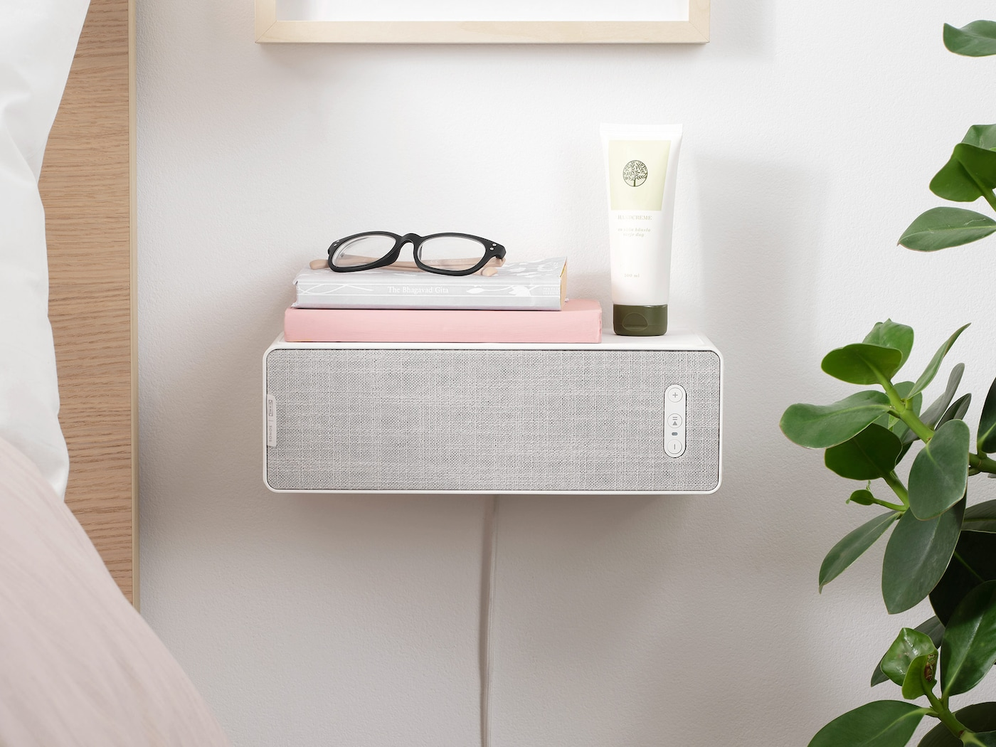 SYMFONISK bookshelf WiFi speaker wallmounted as a bedside table next to a bed.