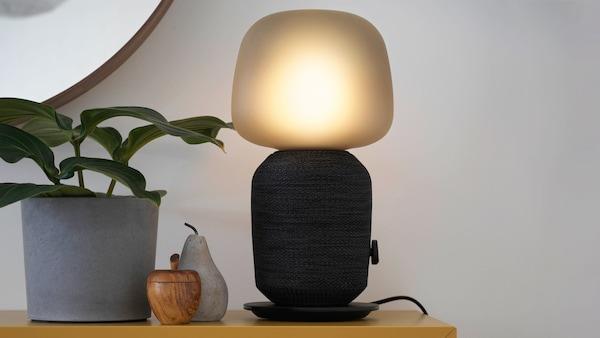 SYMFONISK lámpa hangfal, alma és körte formájú dekoráció, és kaspó a polcon.