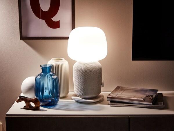 SYMFONISK lampa med wifi-högtalare tillsammans med olika prydnadssaker och tidskrifter.