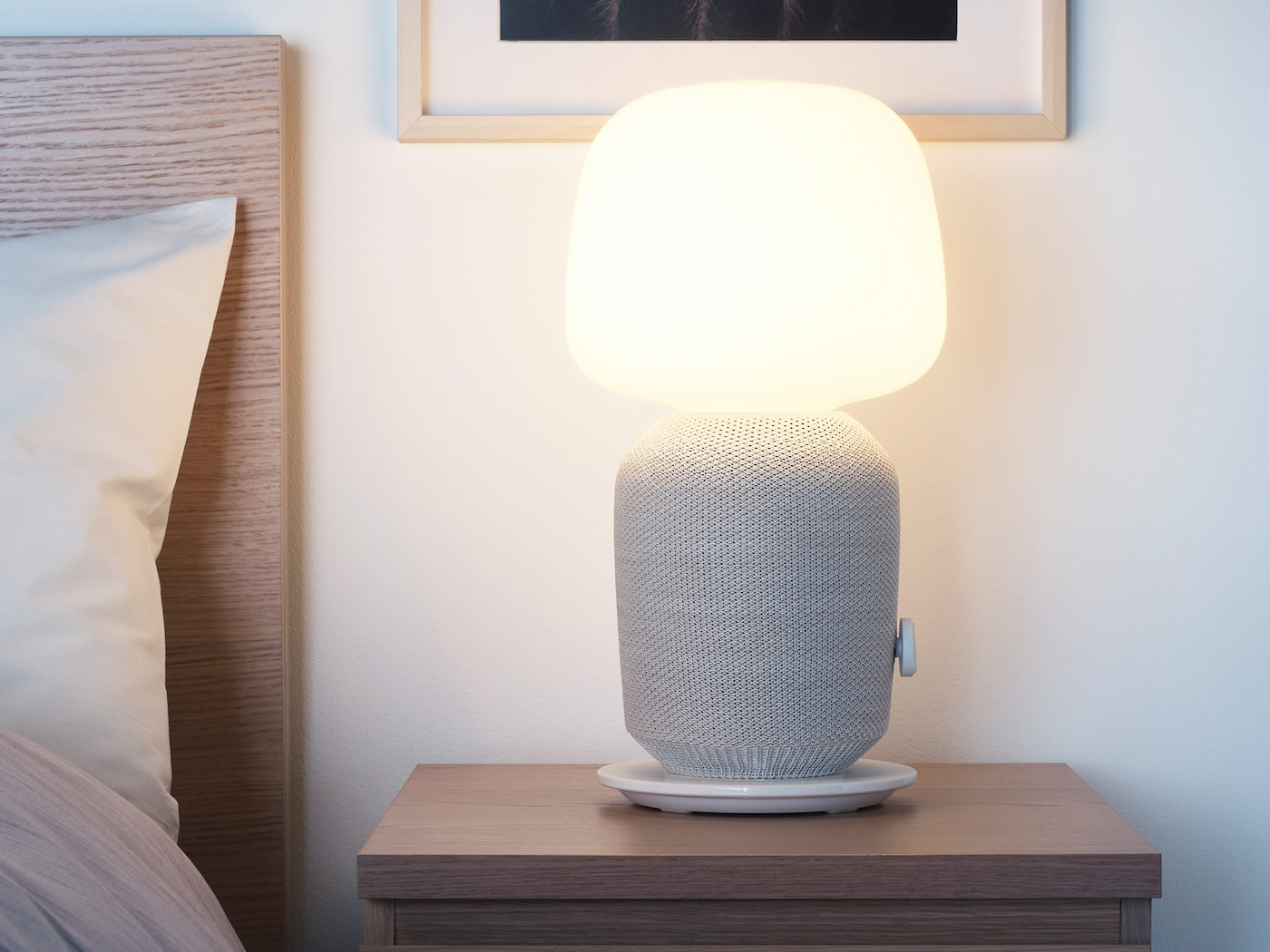 SYMFONISK table lamp with WiFi speaker in white/grey placed on a bedside table next to a bed.