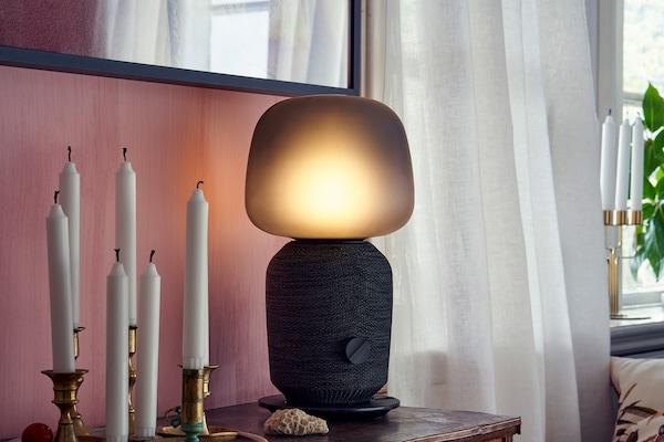 SYMFONISK tafellampspeaker op een nachtkastje, naast een kaarshouder met meerdere kaarsen en een paar gordijnen op de achtergrond.