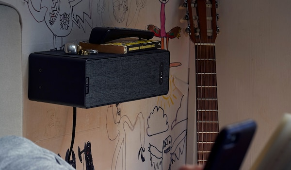 SYMFONISK WiFi bookcase speaker on a shelf, beside a guitar and some graffiti on the wall.