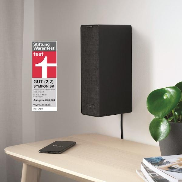 SYMFONISK Wifi Speaker in schwarz an einer weißen Wand über einem Tisch.