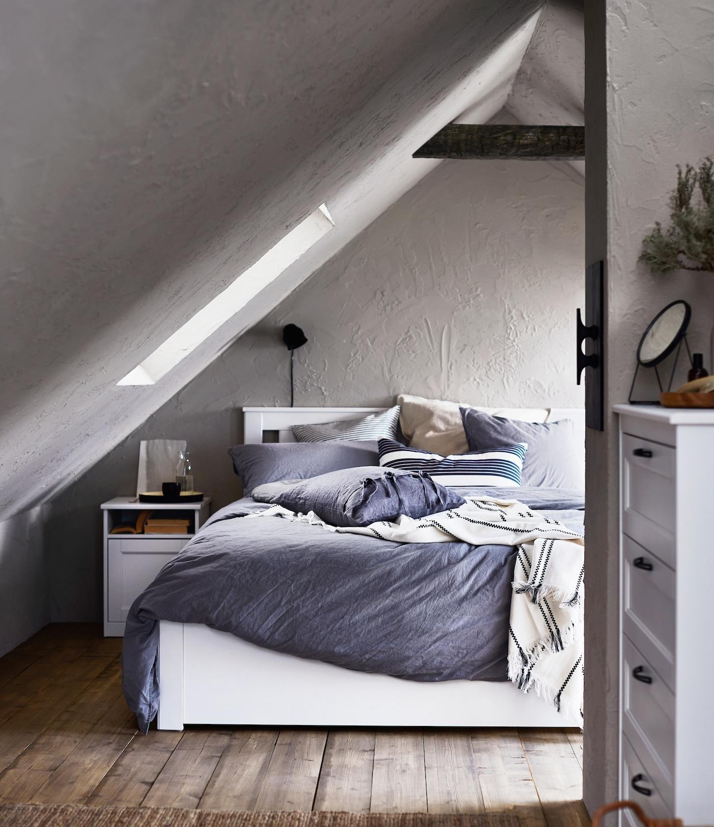 Sypialnia na poddaszu, na łóżku komplet pościeli ÄNGSLILJA, na pierwszym planie na prawo od łóżka stoi komoda SONGESAND