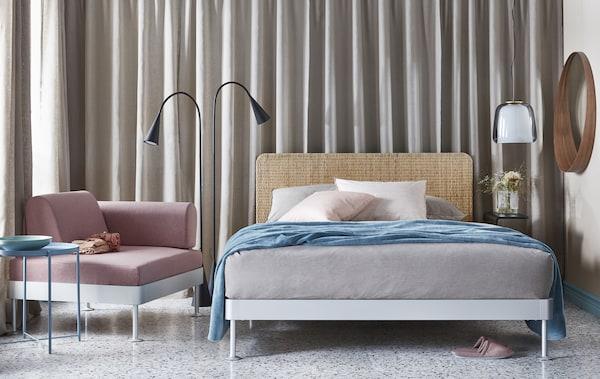 Sypialnia w delikatnych, neutralnych szarościach, beżu i różu z podwójnym łóżkiem, lampą podłogową, fotelem i stolikiem.