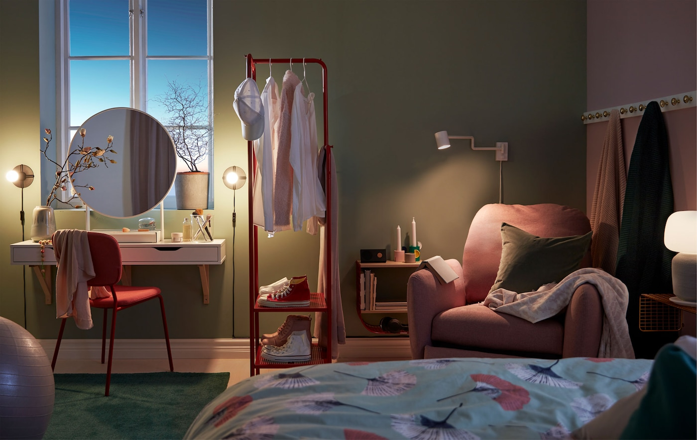 Sypialnia w przyciemnionym świetle z kącikiem do robienia makijażu, wieszakiem na ubrania służącym jako ścianka działowa i kącikiem do czytania z fotelem.