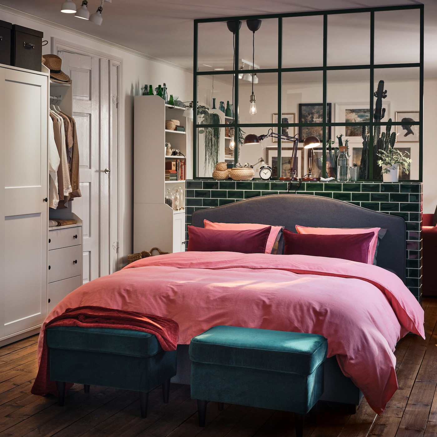 Sypialnia z białymi szafami, szarym tapicerowanym łóżkiem, jasną, brązowoczerwoną pościelą i dwoma zielonymi podnóżkami.