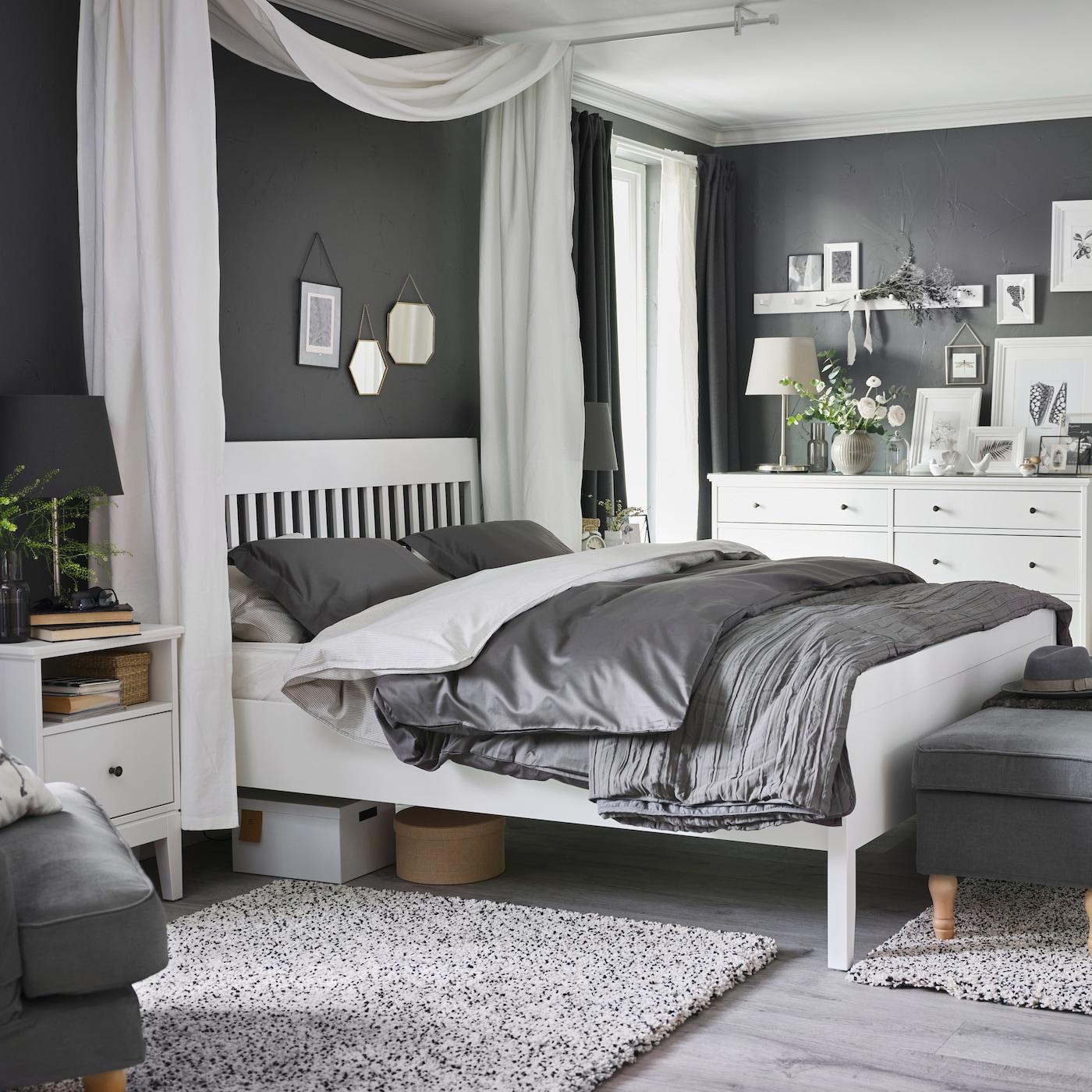 Sypialnia ze stolikiem nocnym, ramą łóżka i komodą IDANÄS w kolorze białym, ciemnoszarą pościelą i dwoma dywanami z długim włosiem.