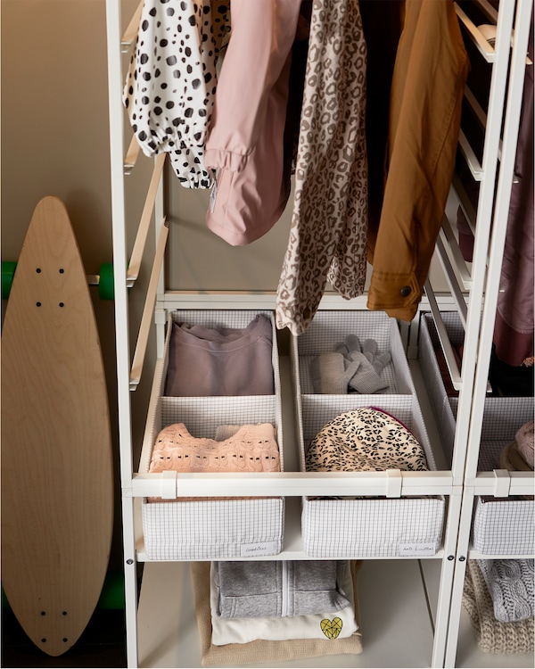 Système de rangement blanc. Dans le bas sont disposées des boîtes à compartiments STUK en blanc et gris garnies de vêtements.