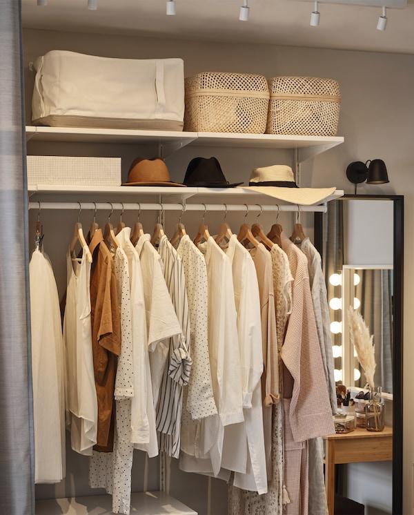 Système de rangement ouvert avec des vêtements suspendus sur une tringle. Sacs de rangement, boîtes et chapeaux rangés sur des tablettes au-dessus.