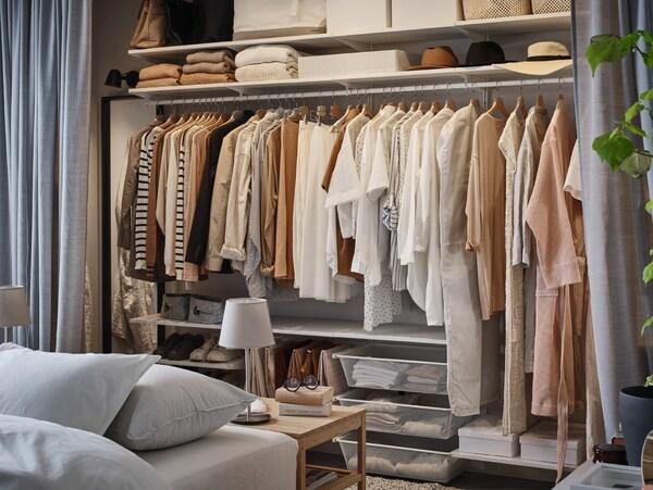 Système de rangements BOAXEL avec de nombreux habits suspendus sur une tringle, plus d'autres vêtements et chapeaux sur des étagères et dans des paniers.