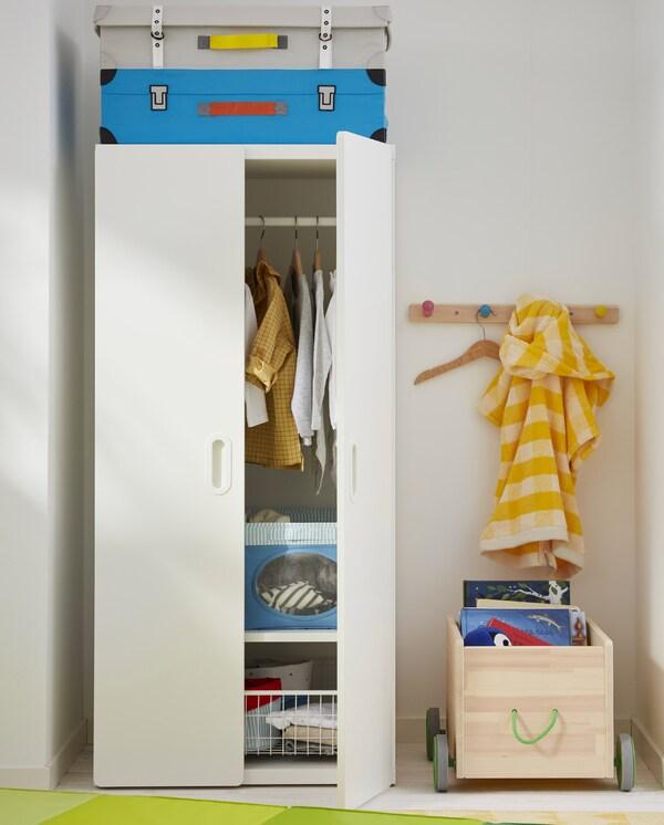 Szafa STUVA/FRITIDS z powieszonymi w środku ubraniami. Obok stoi skrzynia na zabawki FLISAT, a na ścianie zamocowano wieszak z gałkami.