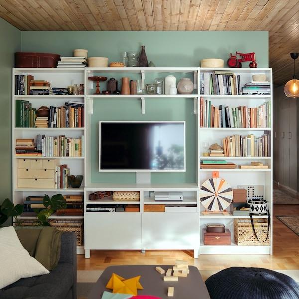 Szafka pod TV z serii BESTÅ z białymi frontami w otoczeniu dwóch regałów BILLY i półek ściennych na zielonej ścianie.
