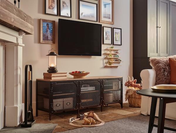 Szafka pod TV z serii FJÄLLBO i wiszące na ścianie telewizor i obrazki w ramkach.