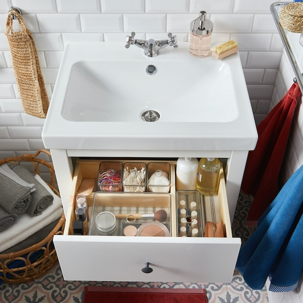 Szafka umywalkowa z otwartą szufladą wypełnioną kosmetykami.