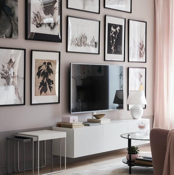 Szafka wisząca pod TV oraz ścian z wiszącym telewizorem i dużymi plakatami w ramach.