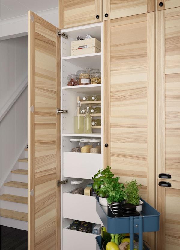 Szafka z drzwiami z litego drewna jesionowego IKEA TORHAMN z wieloma półkami i szufladami w środku, obok stoi ciemnoniebieski wózek RÅSKOG.