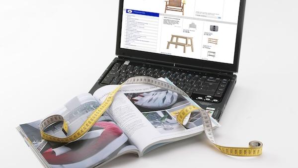 Számítógép, online IKEA tervezővel, rajta katalógussal és mérőszalaggal.