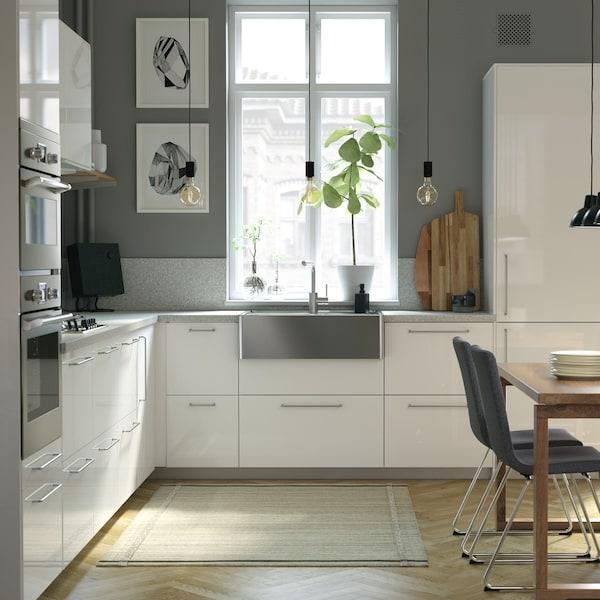 Szara kuchnia z okem i szafkami kuchennymi z białymi frontami.