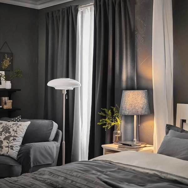 Szara sypialnia z białym łożkiem, szrym fotelem.