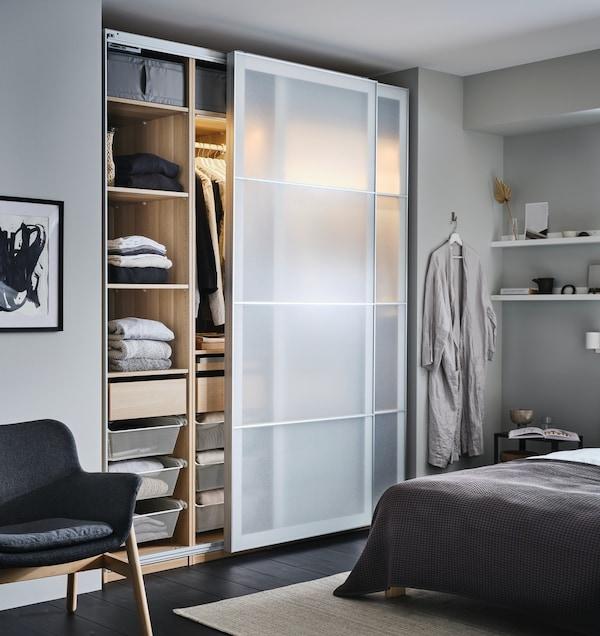 Szaro biała sypialnia z drewnianą szafą z serii PAX z przesównymi drzwiami.