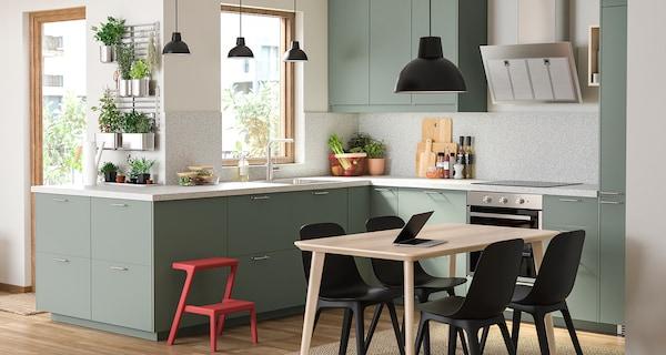 Szarozielona kuchnia, drewniany stół do jadalni, czarne krzesła, czarna lampa wisząca i mnóstwo ziół zawieszonych na drążkach.