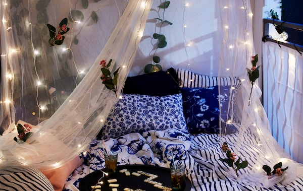 Széles ágy egy zárt erkélyen, virágokkal és LED világító füzérrel díszített szúnyoghálóval; italok és játék egy tálcán.
