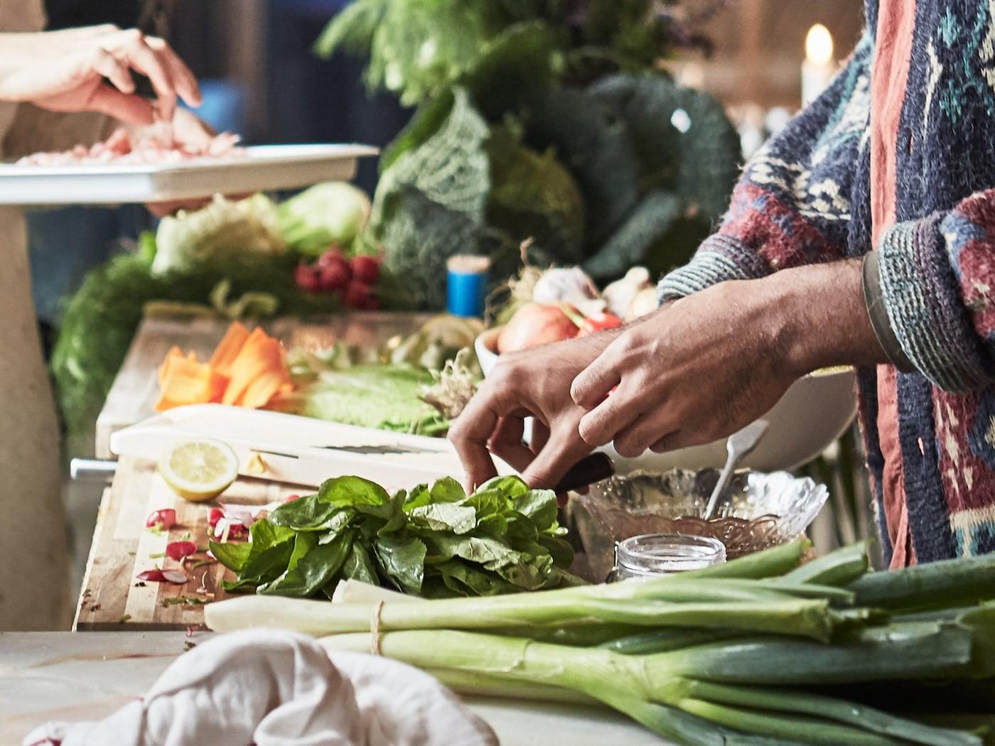 Személy ételt készít a friss zöldségekből.