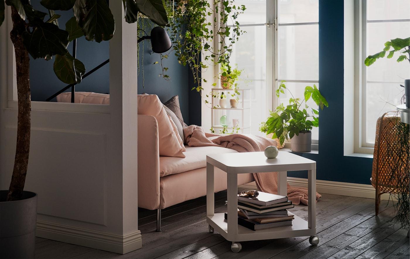 Szezlong przy nasłonecznionych, wysokich oknach. Poduszki, pled i lampa do czytania. Rośliny na parapecie, półkach ściennych i wiszące.