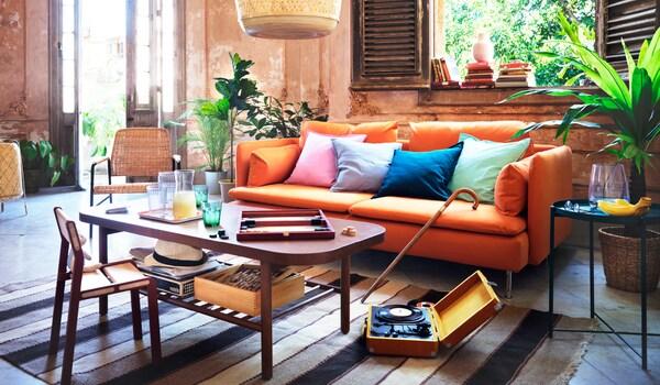 Színes díszpárnák egy narancssárga SÖDERHAMN kanapén a nappaliban. Dohányzóasztal, italokkal és társasjáték.